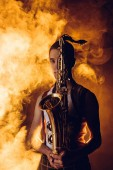 Fotografie young male musician holding saxophone and looking at camera in smoke
