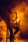 Fotografie Junge expressive Jazzer auf Hocker sitzend und Saxophon spielen