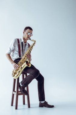 handsome young performer sitting on stool and playing saxophone on grey