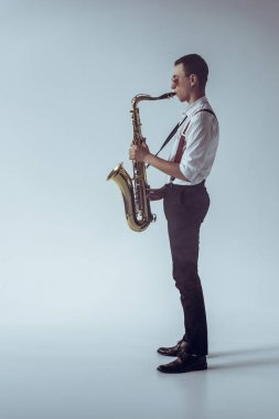 side view of stylish young professional musician playing saxophone on grey