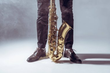 partial view of professional musician standing with saxophone in smoke on grey