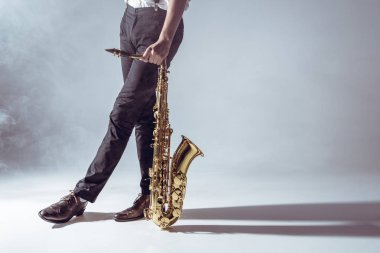 cropped shot of professional musician standing with saxophone in smoke on grey