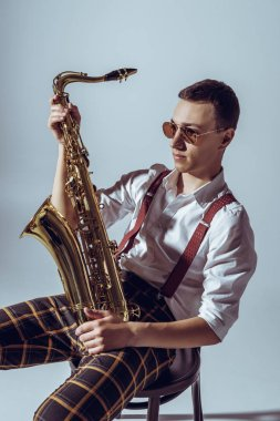 handsome young performer in sunglasses holding saxophone and looking away on grey