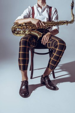 cropped shot of stylish professional musician sitting with saxophone on grey