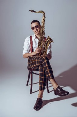 handsome young saxophonist in sunglasses smiling at camera while sitting with saxophone on grey