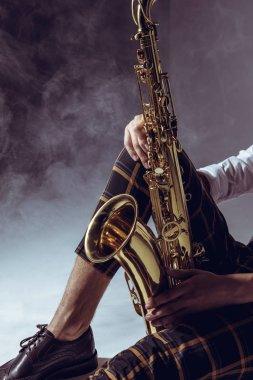 cropped shot of stylish musician holding saxophone in smoke on grey