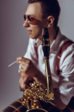 Selective focus of young saxophonist smoking cigarette on grey stock vector