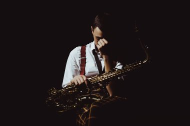young musician holding saxophone isolated on black