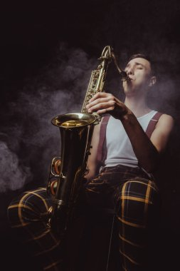 low angle view of expressive young musician playing saxophone in smoke on black
