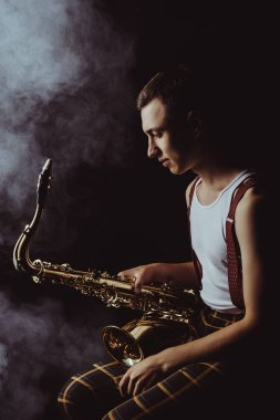side view of stylish young jazzman sitting and holding saxophone in smoke on black