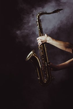 cropped shot of musician holding saxophone in smoke on black