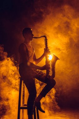 young expressive jazzman sitting on stool and playing saxophone
