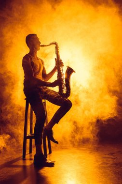 young professional musician sitting on stool and playing saxophone in smoke