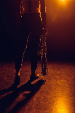 cropped shot of musician holding saxophone on stage
