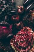 Fotografia vista superiore di cavolo rosso, insalata e cipolle sul tavolo grigio scuro
