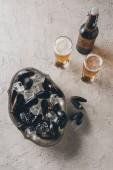 Fotografie Draufsicht der Muscheln in Schüssel, Gläser und eine Flasche Bier auf der Betonoberfläche