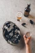 Fotografie Teilansicht des Mannes mit Glas Bier und Muscheln mit Eiswürfeln in Schüssel auf Tischplatte
