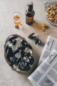 Fotografie Draufsicht der Muscheln mit Eiswürfeln, Bier, Erdnüsse und Zeitungen auf Betonoberfläche