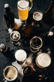 Fotografie top view of arrangement of bottles and glasses of beer on dark wooden tabletop