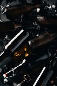 Fotografie ploché vedení ozna.ený otvírák na láhve, skleněné láhve piva a ledové kostky na tmavý stůl