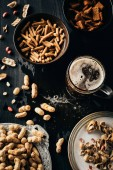 Fotografie top view of table set with snacks and glass of beer on dark wooden surface