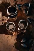 Fotografie Draufsicht der Gläser Bier vom Fass und Muscheln Muscheln auf Rost Oberfläche