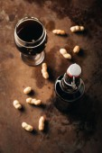 Photo top view of arranged peanuts, bottle and glass of beer on rust tabletop