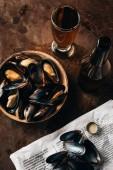 Draufsicht auf arrangiertes Glas und Flasche Bier, Zeitung und Muscheln in Schale auf Rostoberfläche