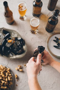 cropped shot of man opening bottle of cold beer at tabletop with peanuts and mussels