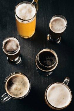 Top view of arrangement of glasses of cold beer on dark wooden tabletop stock vector