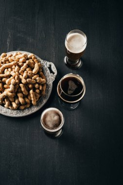 top view of arrangement of mugs of beer and peanuts on metal tray on dark wooden tabletop