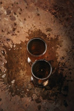top view of glasses of cold beer on rust surface