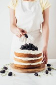cropped shot of woman decorating freshly baked blackberry cake on glass stand on white