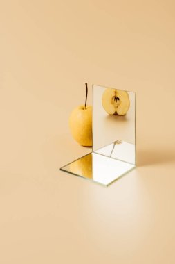 appetizing yellow pear reflecting in two mirrors on beige table