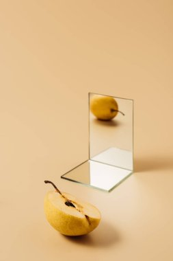 one yellow pear reflecting in two mirrors on beige table