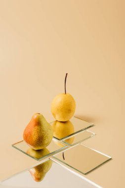 two yellow pears reflecting in mirrors on beige table