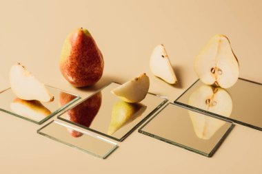 yellow pears reflecting in mirrors on beige tabletop