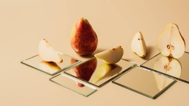 yellow pears reflecting in mirrors on beige table