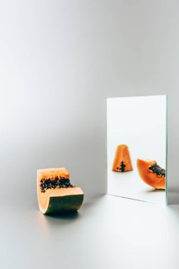papayas reflecting in mirror on white table