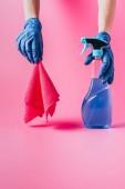 abgeschnittenes Bild einer Putzfrau mit Reinigungsflüssigkeit und Lappen, rosa Hintergrund