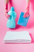 Fotografie partial view of female cleaner in rubber gloves holding laundry liquid and washing powder over stack of clean white t-shirts, pink background