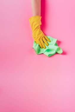 partial view of female cleaner wiping dust by rag, pink background