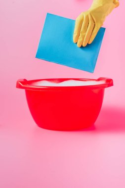 cropped image of woman in rubber glove strewing washing powder in plastic basin with foam, pink background