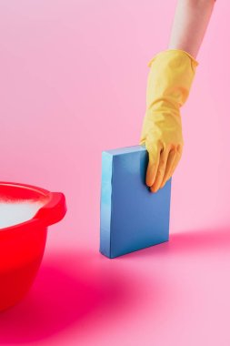 cropped image of woman in rubber glove taking washing powder near plastic basin with foam, pink background