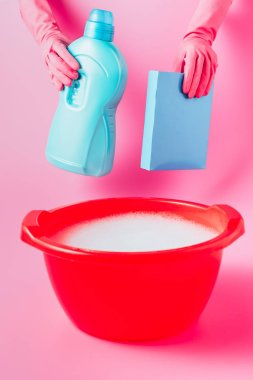 cropped image of female cleaner in rubber gloves holding laundry liquid and washing powder over plastic basin with foam, pink background