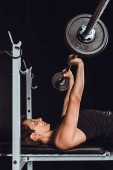 Photo young sportswoman exercising with barbell, black background