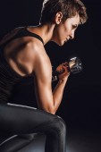 Photo side view of female athlete exercising with dumbbell at gym, black background