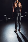 Photo partial view of female athlete doing exercise with barbell at gym, black background