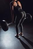 Fotografie Bild von weiblichen Sportler trainieren mit Langhantel in Turnhalle, schwarzer Hintergrund abgeschnitten