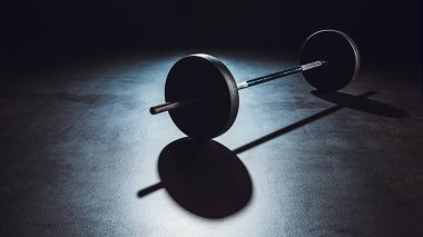 Close up view of barbell on floor with shadow at gym, black background stock vector